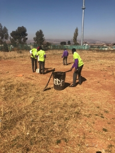 Young reporters cleaning their school's sports fields